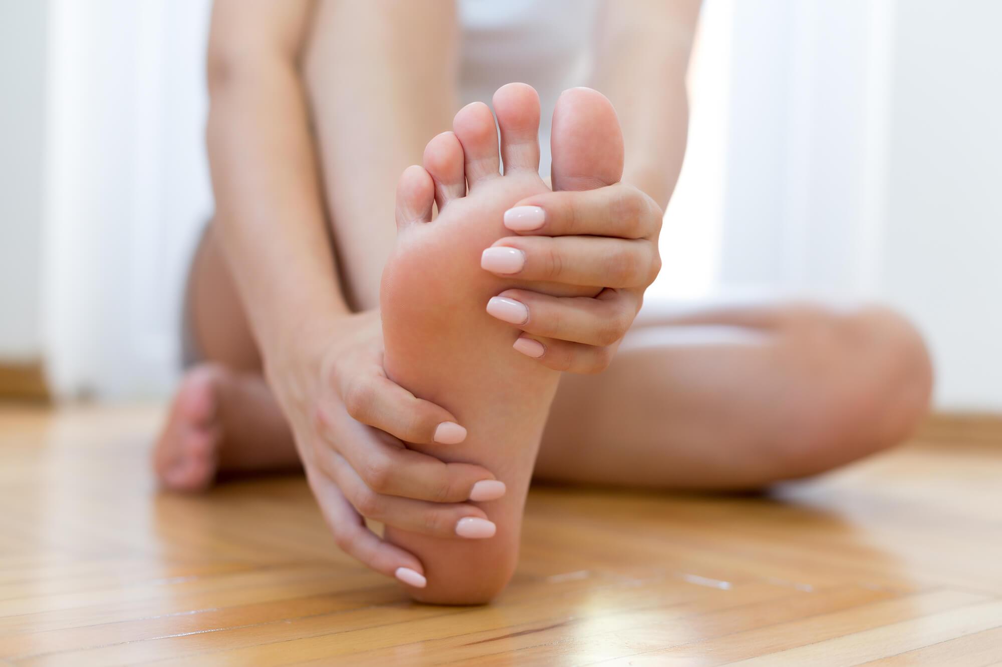Frauenhände-umschließen-Fuß