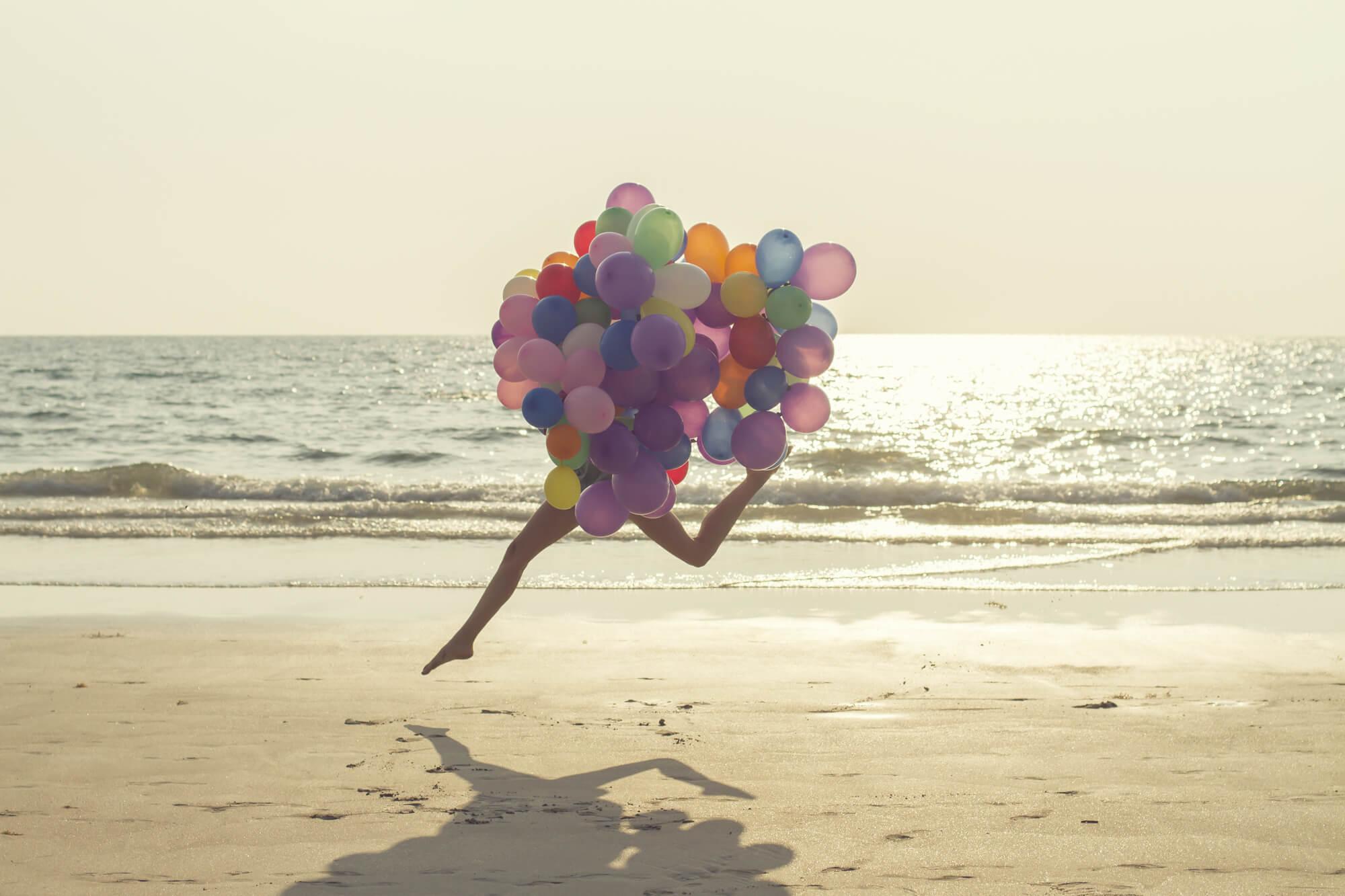 Frau-läuft-am-Strand-entlang-mit-Luftballons-in-der-Hand